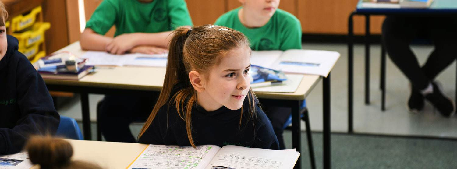 Girl with open workbook paying attention in classroom