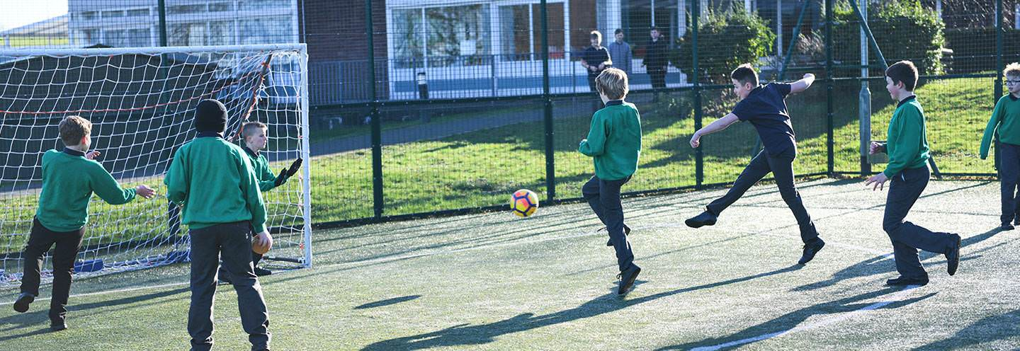 Several boys playing football on the MUGA